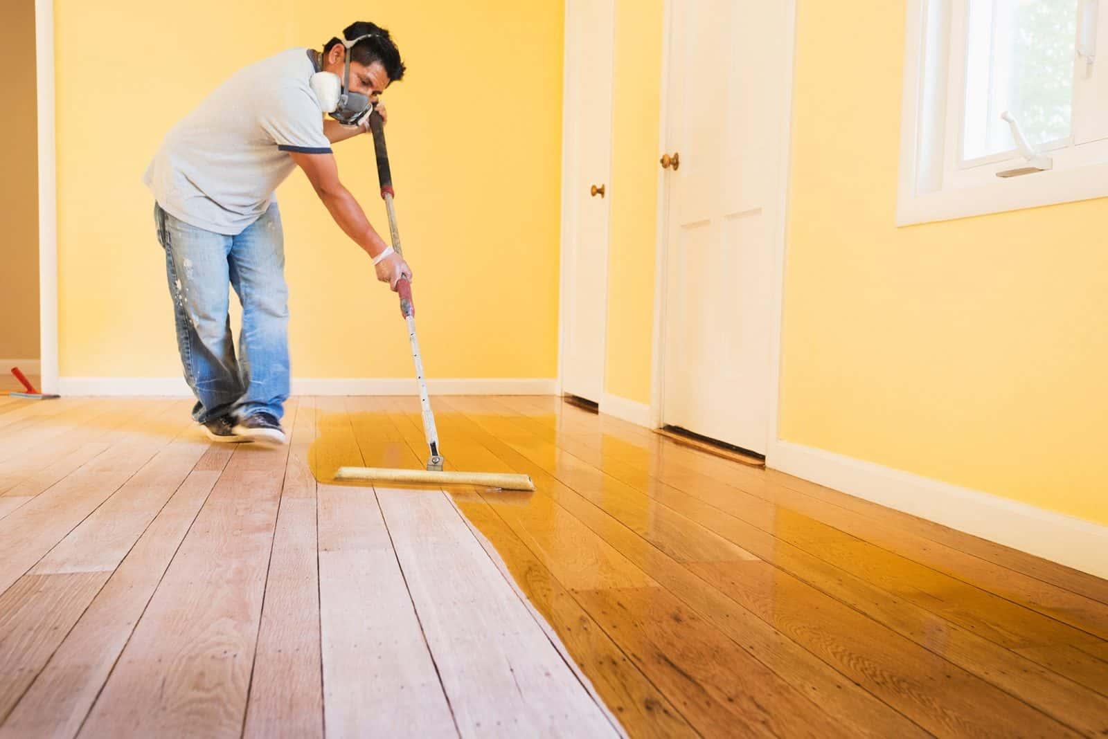 man applying topcoat on hardwood floor
