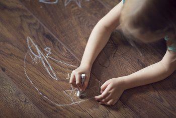child scratching wood laminate